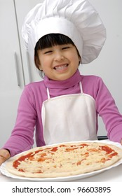 Little girl holding a pizza.Little girl with a chef cap holding a pizza.