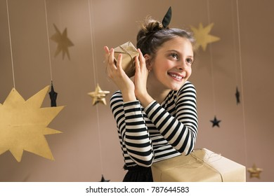 Little girl holding presents in room decorated with golden and black stars