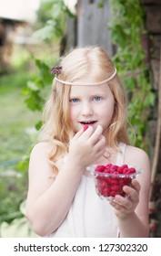 little girl holding raspberries