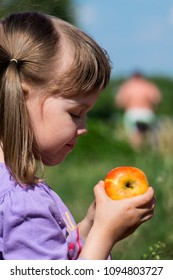 Little girl holding a ruddy apple