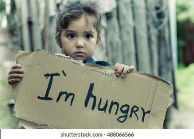 "Little girl holding a sheet of cardboard. On the cardboard label ""I am hungry."" The child is three years."