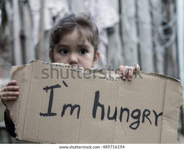 """Little girl holding a sheet of cardboard. On the cardboard label """"I am hungry."""" The child is three years."""