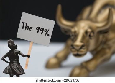 "Little girl holding a sign saying ""The 99%"" in front of a statue known for Wallstreet"