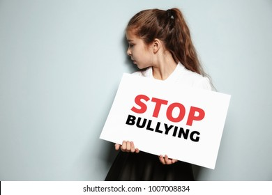 "Little girl holding sign with text ""Stop bullying"" on light background"