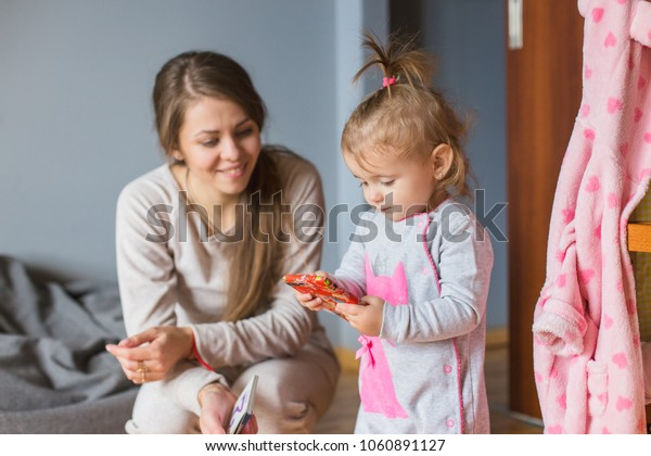 Little  girl holding smartphone, mother looking at her