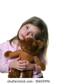 Little girl holding a teddy bear isolated on white and looking into camera with pensive expression