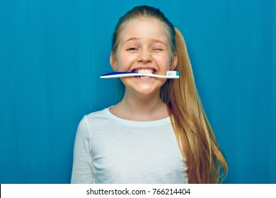 Little girl holding toothy brush with teeth. Blue wall background.