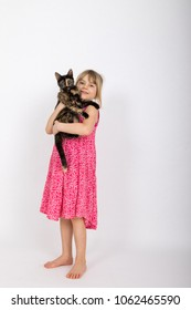 little girl holding a tortoiseshell cat in her arms