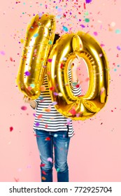 Little girl holding two golden balloons making the 10 number while falling confetti on a pink background. 10th anniversary celebration party.