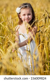 Little girl holding wheat ears in her own hands