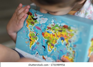 Little Girl Holding a World Map. The Future World is in Children's Hands