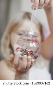 Little girl holds Beautiful Christmas ornament