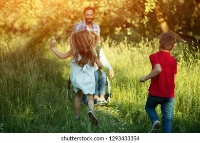 Little Girl Holds A Bouquet Of Wild Flowers And Runs To Her Woman Who Is Sitting In The Wheelchair Folloed By Cute Brother.