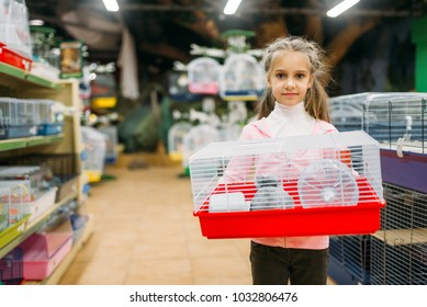 Little girl holds cage for hamster in pet shop