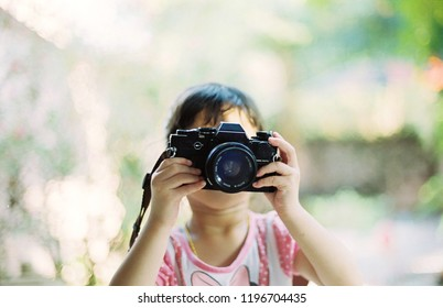The little girl holds the camera and shines happily.