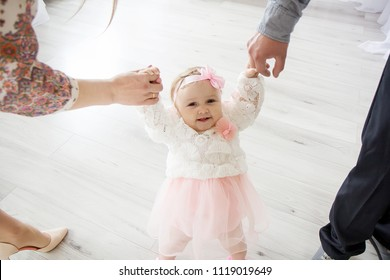 A little girl holds her dad and mother by the hand.