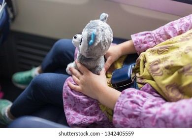 Little girl holds on to stuffed animals while flying on an airplane. Can't see the child's face.