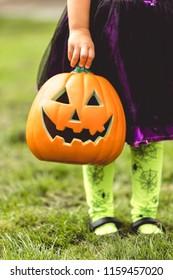Little girl holds an orange jack o lantern Halloween decoration
