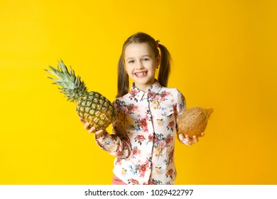 the little girl holds pineapple on a yellow background