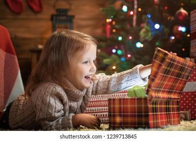 little girl at home with a Christmas tree, presents and candles celebrating christmas