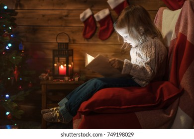 little girl at home with a christmas tree, gifts reading a book sitting in a red armchair