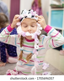 Little girl in home clothes knits from plush yarn with her fingers., indoor