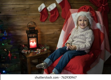 Little girl at home in a decorated room with a Christmas tree and presents