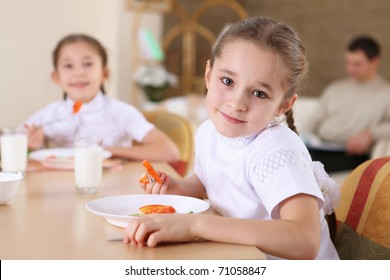 a little girl at home having meal and her family on the background