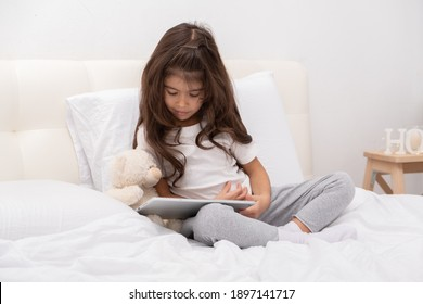 little girl in home wear with teddy bear using tablet sitting on bed.