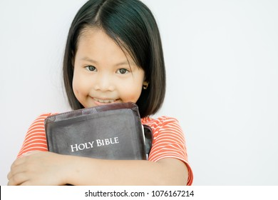 Little girl hug holy bible in the morninga at church in sunday school.concept for faith,spirituality and religion.