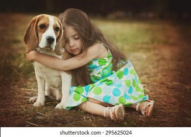 little girl is hugging  dog outdoors