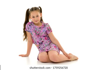 Little girl hugging her knees. sitting on the floor.