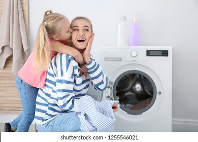 Little girl hugging her mother while she doing laundry at home