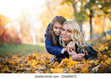 little girl hugging her mother lying in the autumn park