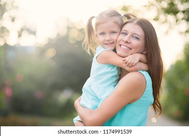 Little girl hugging mother outdoors in park