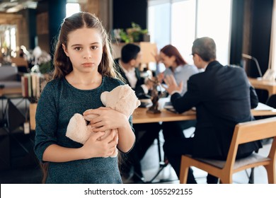 Little girl is hugging teddy bear at office of family lawyer. Registration of guardianship. Family in office of family lawyer.