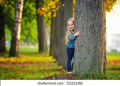 Little girl hugging a tree and smile in park