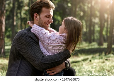 Little girl huggs her father in forest
