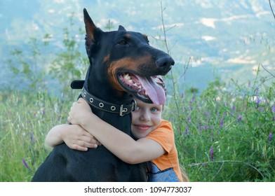 A little girl hugs a Doberman dog.