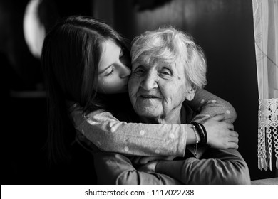 A little girl hugs her grandmother. Black and white photo.