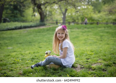 little girl with ice cream on the grass
