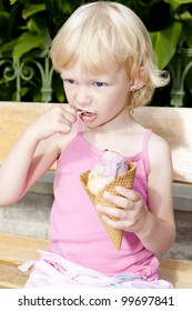little girl with ice cream sitting on bench