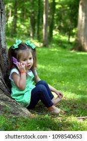 Little girl immerses herself in role playing, as she chats to her imaginary friend on her play telephone.  She has pigtails and green hairbows.