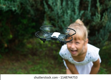 A little girl indulges and plays, takes herself to the copter and places the video on her blog. STEM education. Dron, bot, robotics technology.