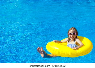 Little girl with inflatable rubber ring having fun in swimming pool. Place for text.