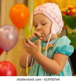 The little girl inflates mottled paper whistle birthday.