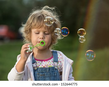 The little girl inflates soap bubbles