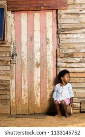 Little girl infront of a wooden shack wih a serious expression on her face