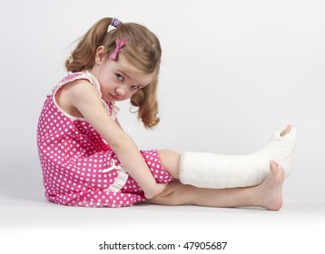 Little girl injured with broken ankle sitting on white background.