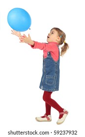 little girl in jeans dress playing with blue balloon side view isolated on white
